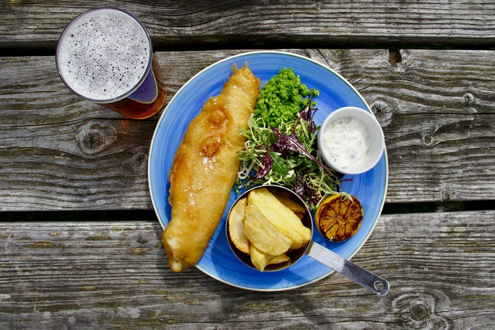 Plate of fish and chips, a popular British dish, with a pint of beer on the side.