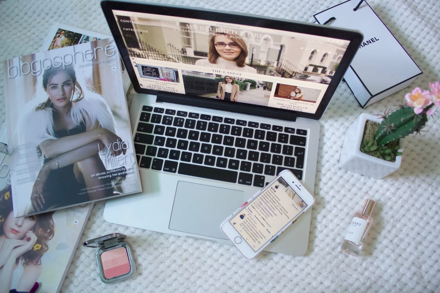 Laptop open on a bed, surrounded by makeup, perfume and magazines. The screen is open on My Blurred World, Elin Williams' lifestyle blog.